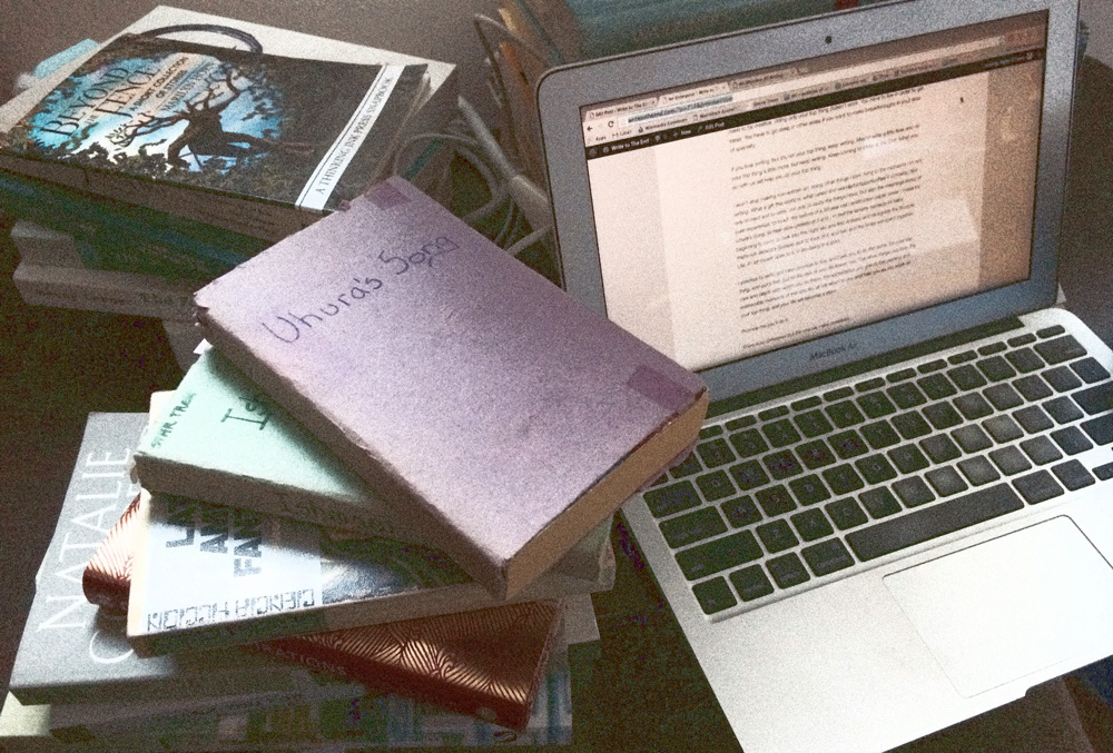 photo of laptop and books, including Uhura's Song